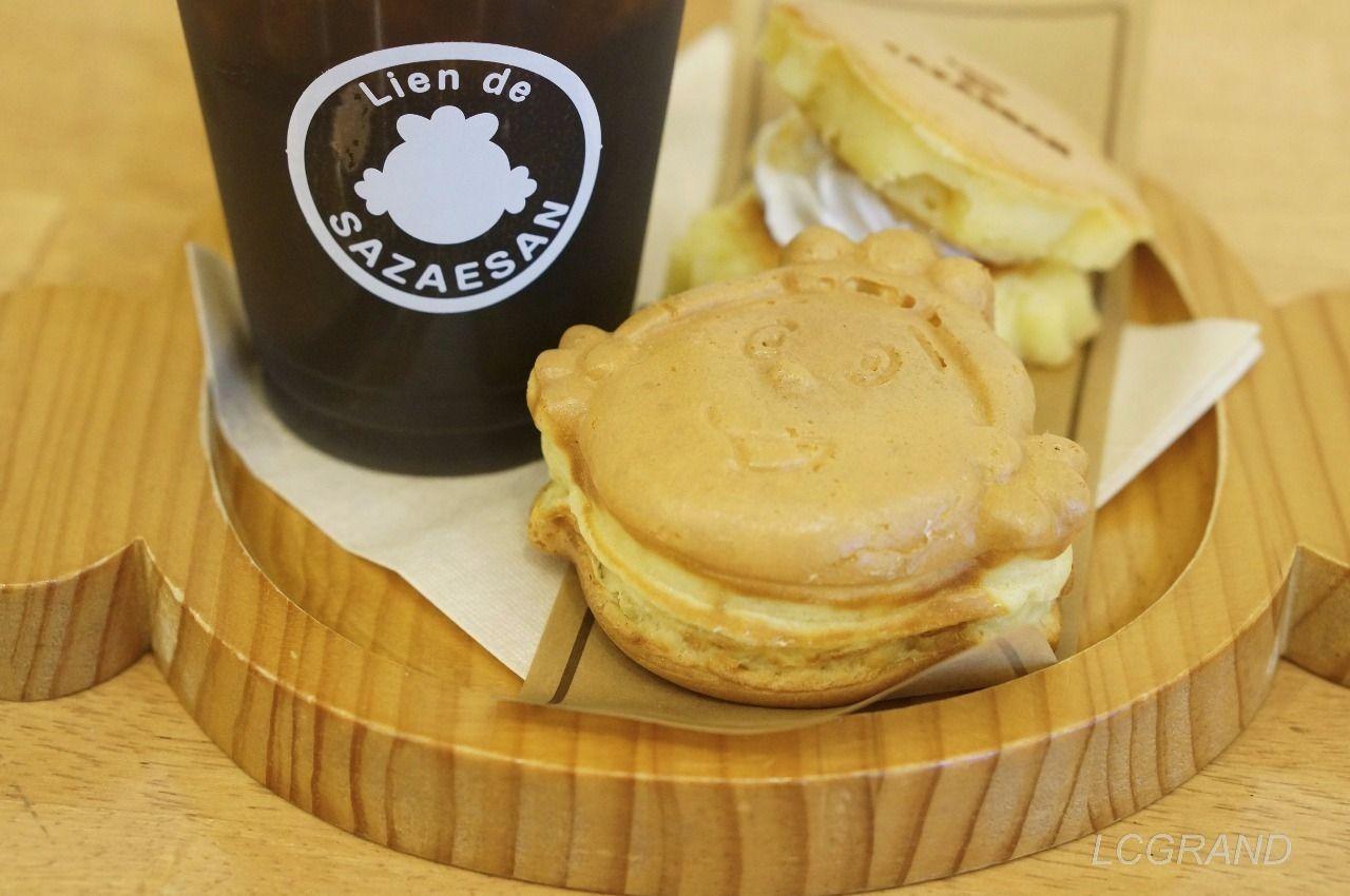 リアン・ドゥ・サザエさん (Lien de SAZAESAN) のパンケーキとサザエさん焼きとアイスコーヒーがサザエさんの形をしたお盆に乗せられて提供されます。